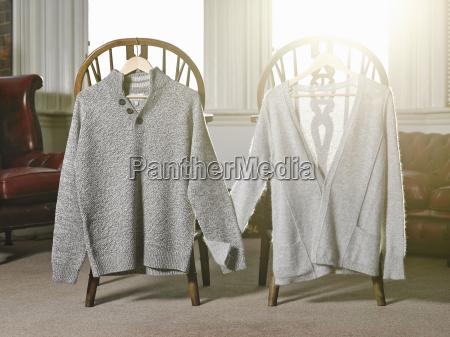 zwei pullover auf kleiderbuegeln die haende