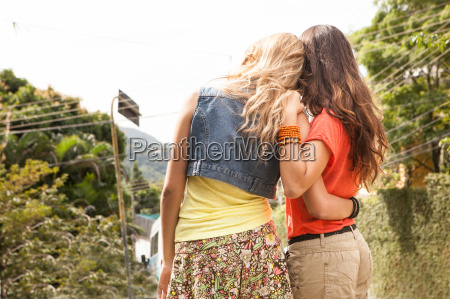 women hugging and looking into distance