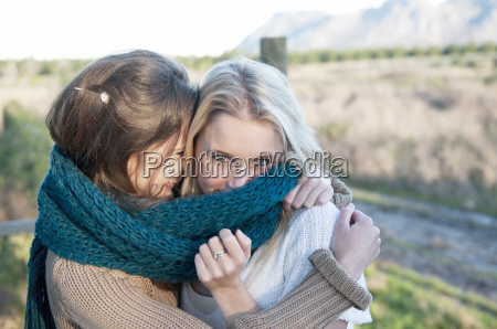 two young women wearing knitted scarf
