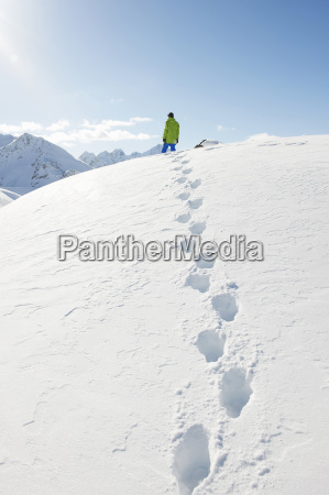 man standing in snow with footprints