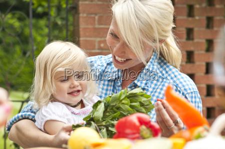 mother and toddler daughter preparing food