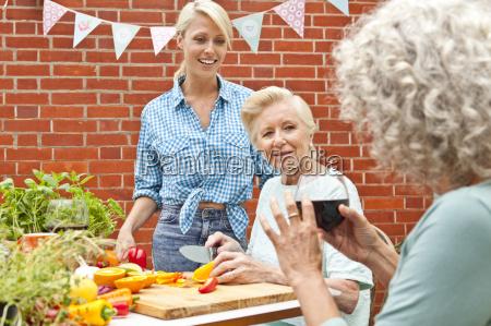 three generation women chatting while preparing