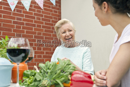 two women chatting while preparing food