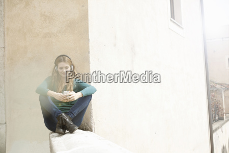 young woman sitting cross legged listening