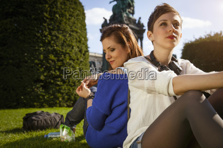two young adult women sitting back