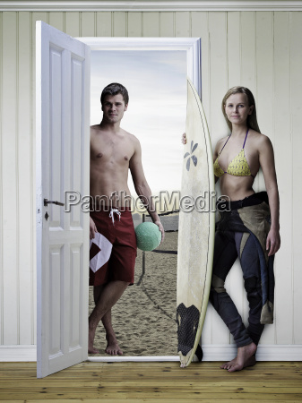 couple with surfboards in new house