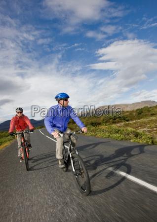 men riding bikes on rural road
