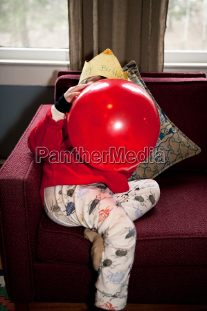 boy blowing up red birthday balloon