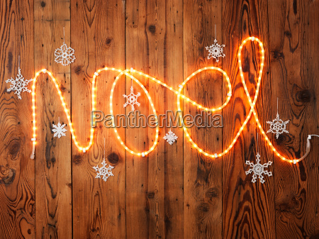 christmas lights spelling noel against wood