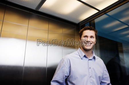 business man in elevator smiling
