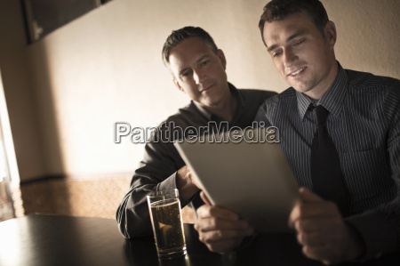 two business colleagues looking at digital