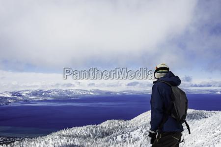 young male hiker enjoying view lake