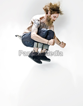 young man with tattoos jumping mid