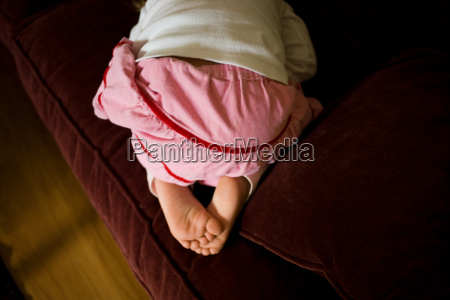 young girl kneeling on sofa