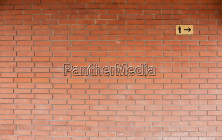male toilet sign on brick wall