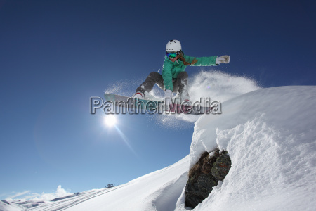 young woman jumping with snowboard mayrhofen