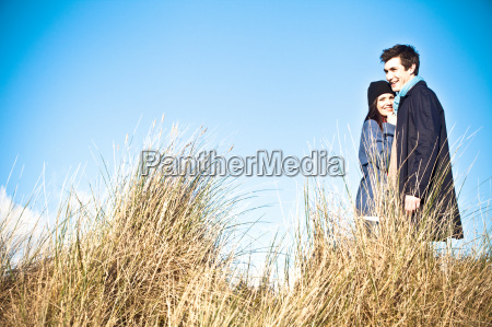 couple standing in sand dunes bournemouth