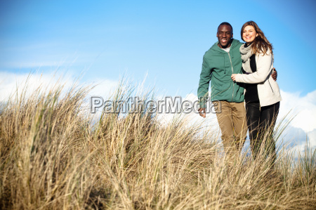 young couple strolling in sand dunes