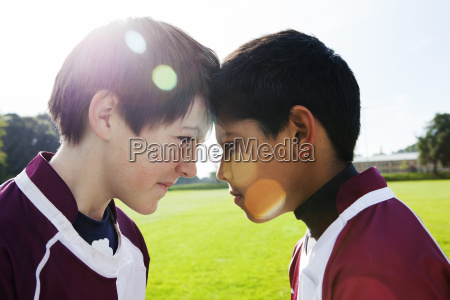 two teenage schoolboys face to face