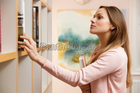 young woman choosing book from bookcase