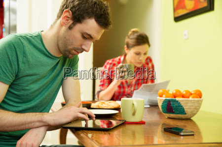 young couple at breakfast man using