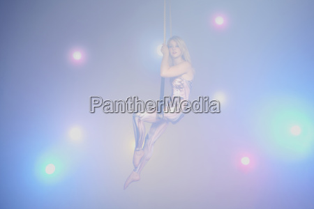 young woman sitting on trapeze
