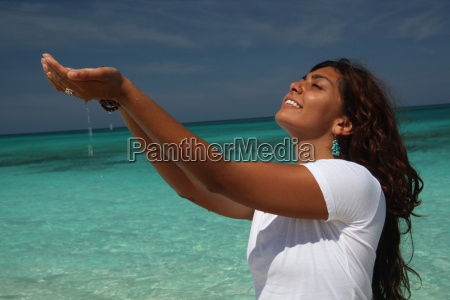 young woman on beach with hands