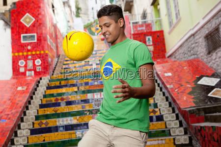 young man wearing brazil top doing