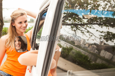 young women talking through camper van