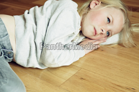 young girl lying on wooden floor