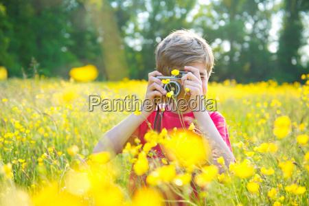 boy standing in long grass taking