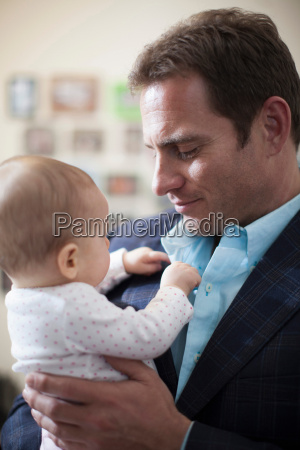 businessman holding baby daughter