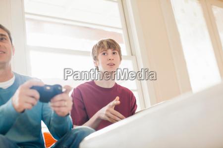 vater und erwachsener sohn beim videospiel