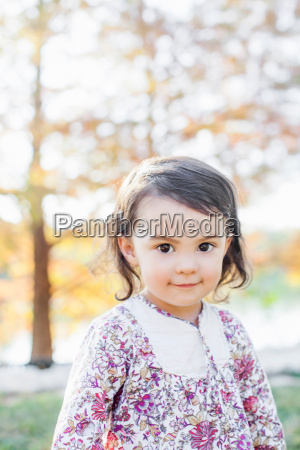 child in woods looking at camera