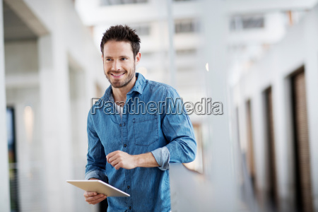 man with digital tablet looking away