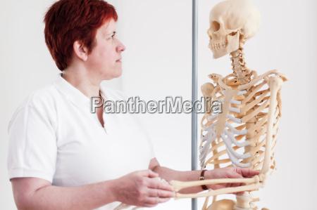 woman holding arm of model skeleton