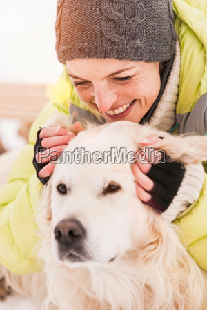 woman in knit hat stroking dog