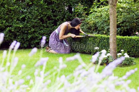 woman pruning plants in backyard