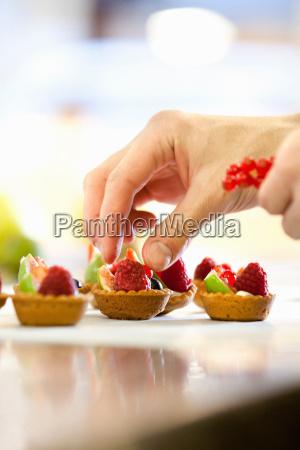 baker making fruit tarts in kitchen
