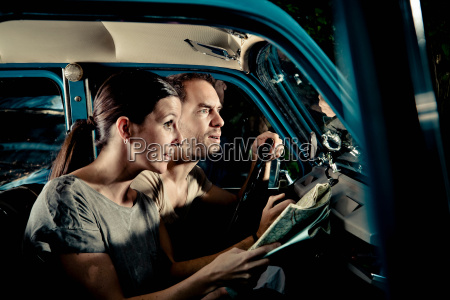 couple reading map in car at