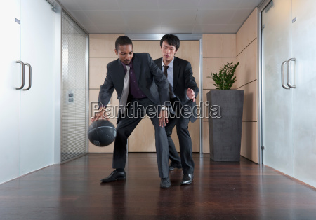 businessmen playing basketball in office