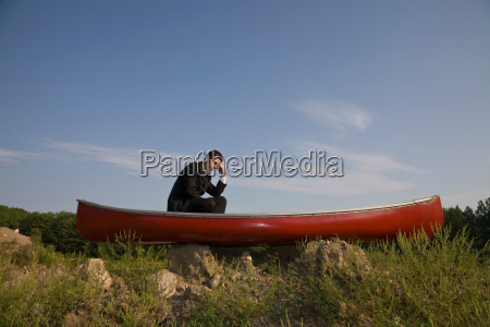business man stranded in canoe