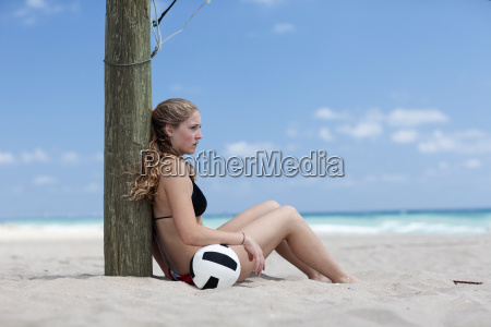 young woman on beach with volleyball