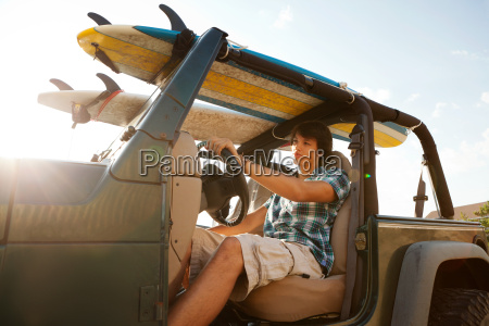 teenager driving jeep with surfboards