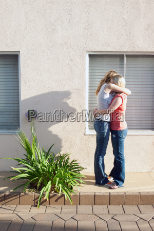 young lesbian couple embracing by window