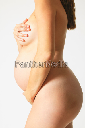 nude pregnant woman covering herself