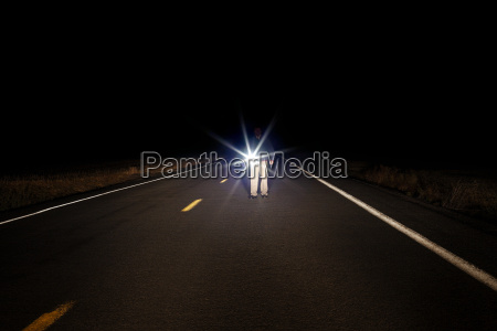 man walking along empty road with