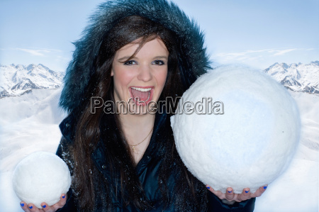 young happy woman with two snowballs