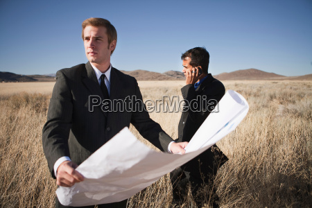 2 men with plans in field