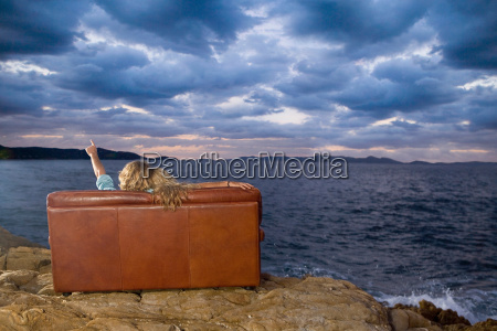couple on couch look at sea